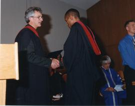 John H. Unger giving William Mbugua his diploma