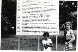 Adult and child in front of sign