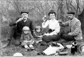 Mr. Hansel, Anna (Wiens) Rempel and her husband, Dietrich Rempel having a picnic outside.