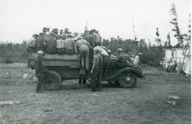 Men piled on back and wheelwells of a truck