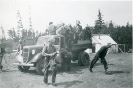 Men getting out of and off the back of a truck