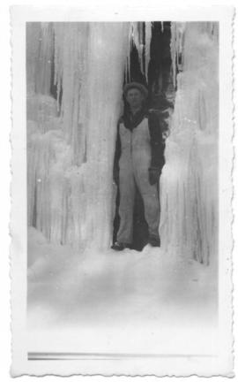Unidentified man standing in front of huge icicles.