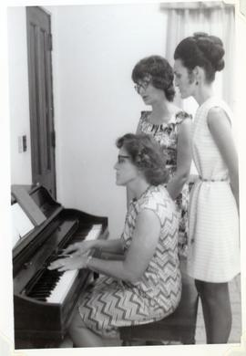 Three women at a piano