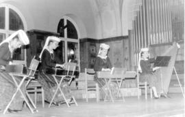 Four women performing on musical instruments