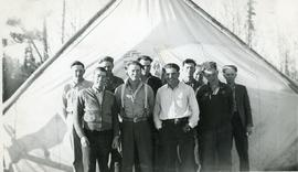 Ten smiling men in front of a tent