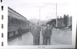Four men standing in front of a train, J.J. Thiessen and others