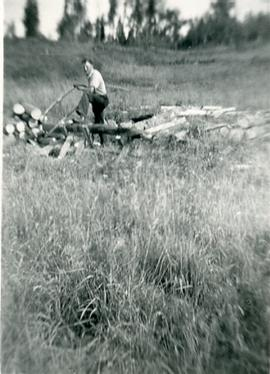 A man cutting logs