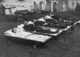 Photo of four men and one woman in caskets