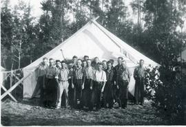 18 men posing for a photo outside a tent
