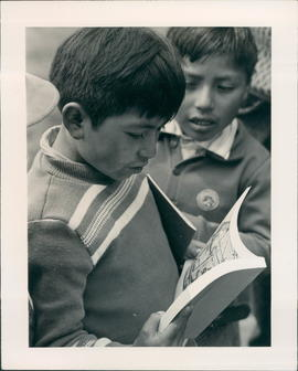 Two young fellows looking at the new Bible story book. Report by Stan & Marian Houghton