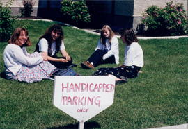 four young women seated on grass near No Parking sign