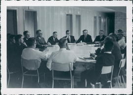 Mission Board meeting. Facing camera from left, Ben Friesen, Abe Unger, Arnold Fast, Milton Fast, Chair, P.L. Friesen; others unidentified