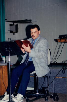 Corey Herlevsen, speaking while looking at Bible