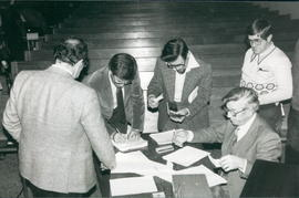Arnold Reimer (seated) collecting membership dues
