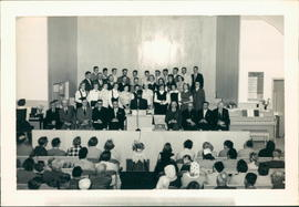 Seated: Ministers Dave Froese & Abe Leiding (2nd & 3rd from right) and Hans Dyck, pastor, Emmaeus Church (4th from left); visiting Rhineland choir is singing