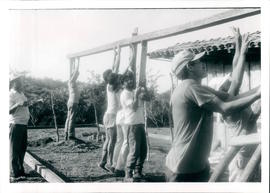 A crew of volunteers raising a beam to support the roof of a new home