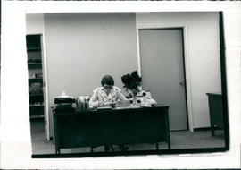 Martha Kroeker, Secretary/Receptionist, at her desk in new building