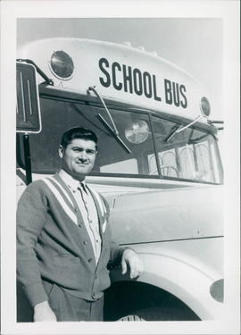 Andrew Friesen, pastor, in front of school bus he drives to supplement income