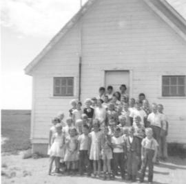 A group of children with their teacher standing in front of a building