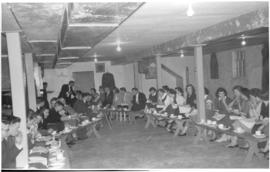 Youth seated and eating along the outside walls of Steinbach Mennonite Church basement