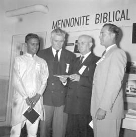 , J. J. Thiessen & Samuel Stephen stand in front of MBS display panels with two other men