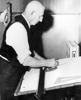 Abraham M. Bowman at his drawing board after the