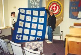 Debbie and Albert Butt displaying a quilt