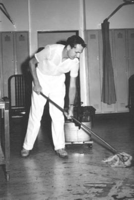 A young man serving as a CO mops the floor in a hospital