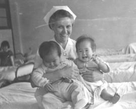 A nurse holds two Taiwanese babies on her lap.