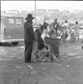 An Amish man pushing an Amish woman in a wheelchair at the Relief Sale in New Hamburg, Ontario