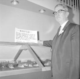 J.J. Reimer, pres. of Mennonite Historical Society of Manitoba stands beside a replica of the vil...