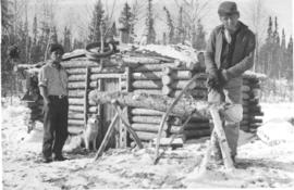 Indigenous young men in front of a log house