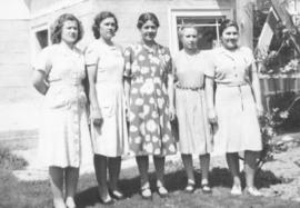Five young women stand in front of a house