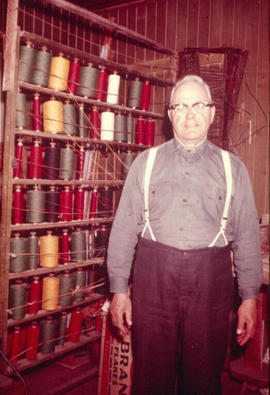 Amos Bowman, carpet maker, standing in shop