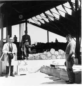 Dr. W. Fretz stands beside the cornerstone before