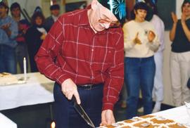 Ralph Lebold cutting a birthday cake for Conrad Grebel College