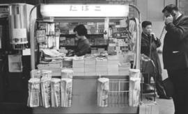 A news stand (kiosk) with a woman behind the