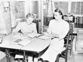 Janet Brunk doing her homework at the table with her mother