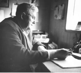 A. A. Wiens at his desk in 1964