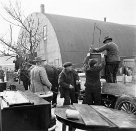 Men removing items from a horse-drawn wagon at the Elmira Pig Fair in Elmira, Ontario