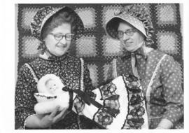Alice Snyder & Pearl Cressman in centennial costume displaying a pyjama doll