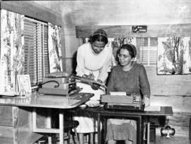 Two women using typewriter and reviewing notes