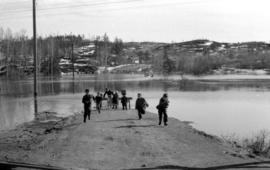 Children running away from flooding river in Markstay, Ontario in March 1951