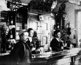 Copy of two men standing behind and one in front of the counter in the St. Jacobs Hotel, St. Jacobs, Ontario