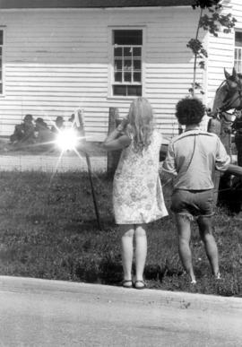 Tourists photographing boys outside of the Martin Mennonite Meetinghouse