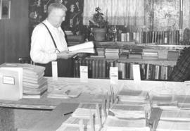 A. A. Wiens is reading & sorting correspondence