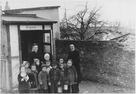 A group of young children stand at the entrance to a building
