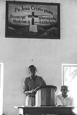 A church leader likely giving a sermon or reading