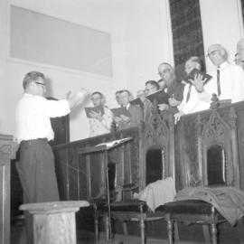 A  group of men rehearsing in the choir loft,