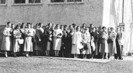 Large group of women and a few men likely standing beside a church building